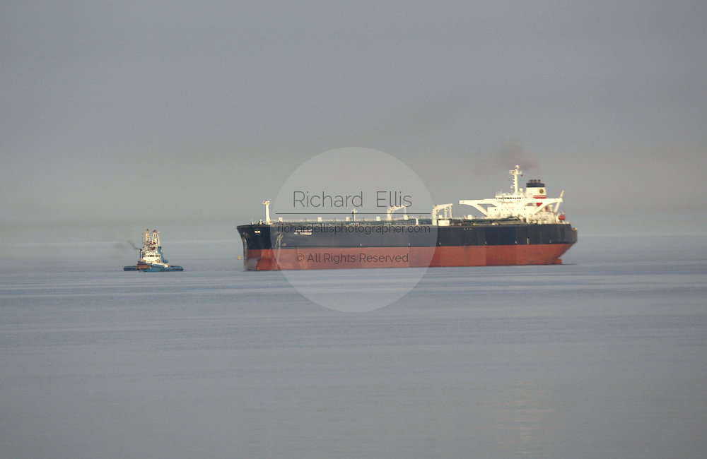 An empty oil tanker is pulled by a tug to an oil loading station along the Persian Gulf coast of Kuwait.