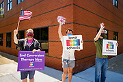 """24 JULY 2020 - DES MOINES, IOWA: People from an office building near the State Capitol cheer for Iowa teachers driving past their office during a teachers' protest to reopen Iowa schools. Hundreds of teachers from across Iowa came to the state capitol Friday to protest Governor Kim Reynolds' order that school must reopen with in person education and minimized the potential for """"distance learning."""" The event was one of the largest COVID-19 protests in Iowa since the pandemic started, more than 740 teachers signed up to attend the protest. After the protest officially ended, many teachers left the capitol and drove to Gov. Reynolds' residence, where they drove around her mansion and honked horns. Some people left notes on the entrance to the governor's residence. Gov. Reynolds ordered the school reopening last week, but according to teachers, the state has not implemented health guidelines or bought protective equipment like face masks in the quantity required to slow the spread of the Coronavirus (SARS-CoV-2). Iowa's numbers of COVID-19 infections are up statewide.         PHOTO BY JACK KURTZ"""