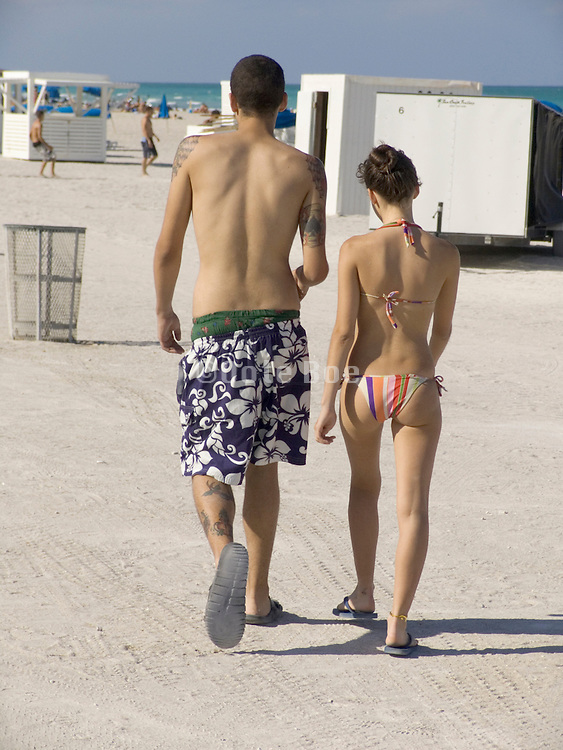 Two young people walking on the beach Miami USA