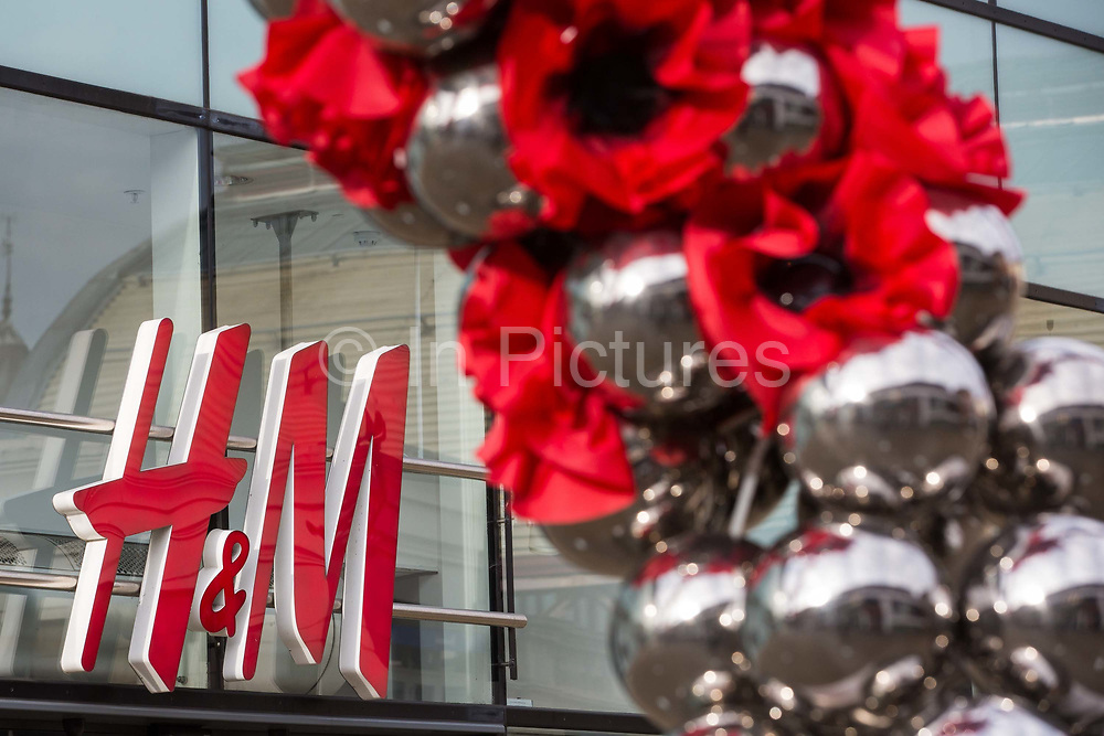 """Remembrance poppies are displayed in front of a branch of Swedish fashion chain H&M (Hennes & Mauritz AB) on the second day of England's second coronavirus lockdown on 6 November 2020 in Windsor, United Kingdom. Only retailers selling """"essential"""" goods and services are permitted to remain open to the public during the second lockdown provided that they follow coronavirus guidelines and make their premises COVID-19 secure."""