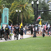 Orlando police officers on bikes observe protesters at a rally to end the stay at home order and open businesses and schools at Lake Eola on Saturday April 25, 2020 in Orlando, Florida.  Governor Ron DeSantis signed an executive order that restricts non-essential employees and businesses from opening and working. (Alex Menendez via AP)