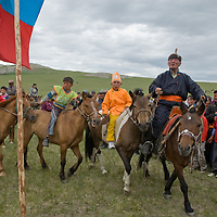 A clan elder (who is singing) leads young, costumed  winners of a 20km horseback raceat a traditional naadam festival on a remote pass near Muren, Mongolia. Many of the youngsters rode barefoot and bareback to save weight.
