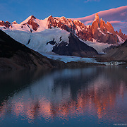 Golden mountain peak and pink sky light up with first light upon Cerro Torre and reflect on the lake below in Patagonia, Argentina.