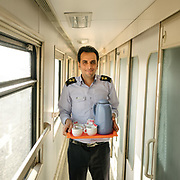 Train staff. Overnight train from the holy city of Mashhad to the desert city of Yazd, known for its  zoroastrian community and wind towers.<br /> <br /> Travelling over 4000km by train across Iran. An opportunity to enjoy Persian hospitality, discover Iran's ancient cities and its varied landscapes, from deserts to mountains.