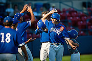 Eric Ashcraft celebrates his two-run homerun at home plate with the rest of the Moline American Legion baseball team during the first inning of Friday's game against Branford, CT at Avista Stadium in Spokane, WA.