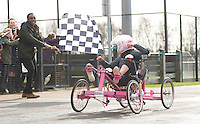 Blue Peter presenters have gone head-to-head on their personally modified bikes in a cycle race for Sport Relief 2014.  Ore Oduba waves the chequered flag as Lindsey Russell crosses the finish line<br /> <br /> Photo by Chris Vaughan/CameraSport<br /> <br /> Commercial - Sport Relief -  publicity shoot - Tuesday 4th March 2014 - University of Central Lancashire Sports Arena - Preston<br /> <br /> © CameraSport - 43 Linden Ave. Countesthorpe. Leicester. England. LE8 5PG - Tel: +44 (0) 116 277 4147 - admin@camerasport.com - www.camerasport.com
