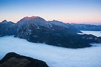 Watzmann (2713m) rises above fog inversion layer at sunrise, viewed from summit of Jenner, Berchtesgaden national park, Bavaria, Germany