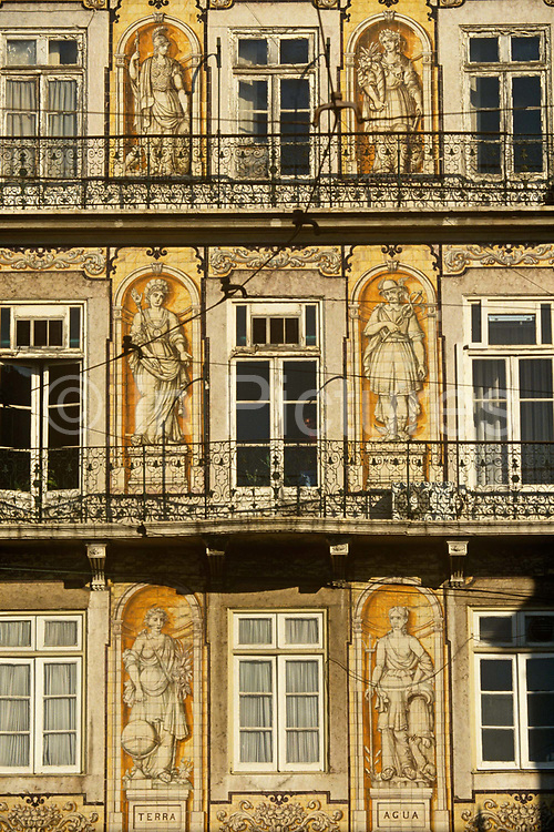 Old apartment and iron balcony architecture in Lisbon's old Arabic Alfama district. Murals of classical Portuguese figures adorn the plaster walls next to crumbling windows and balconies which have the look of vintage from a former era in Lisbon's capital. Alfama is the oldest district of Lisbon, spreading on the slope between the Castle of Lisbon and the Tejo river. Its name comes from the Arabic Al-hamma, meaning fountains or baths. It contains many important historical attractions, with many Fado bars and restaurants.