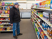 "25 FEBRUARY 2020 - BUTTERFIELD, MINNESOTA: KERMIT LEET, a retired teacher, looks at fruit juices in the grocery section of the True Value Hardware Store in Butterfield, MN, a farming community of about 500 people 130 miles southwest of the Twin Cities. The town has been a ""food desert"" for 10 years after its only grocery store closed in 2010. Barb Mathistad Warner and Mark Warner purchased the True Value store in Butterfield in December, 2018 and started selling groceries in the store in May, 2019. For residents of Butterfield going to a grocery store meant driving 10 miles to St. James, MN, or 20 miles to Windom, MN, the two nearest communities with grocery stores. The USDA defines rural food deserts as having at least 500 people in a census tract living 10 miles from a large grocery store or supermarket. There is a convenience store in Butterfield, but it sells mostly heavily processed, unhealthy snack foods that are high in fat, sugar, and salt.   PHOTO BY JACK KURTZ"