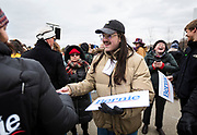 "Erik Kramer passes out ""Bernie"" posters before a rally for Democratic 2020 presidential candidate Bernie Sanders at James Madison Park in Madison, WI on Friday, April 12, 2019."