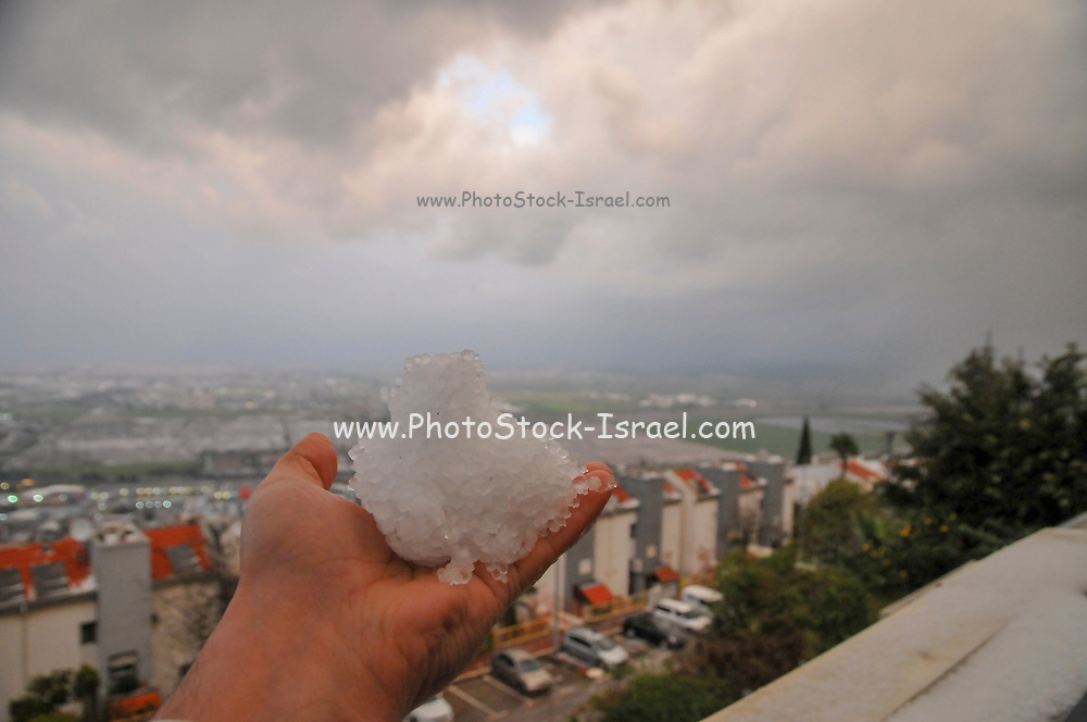 Hand holding hail after a hail storm, Photographed in Haifa, Israel in March