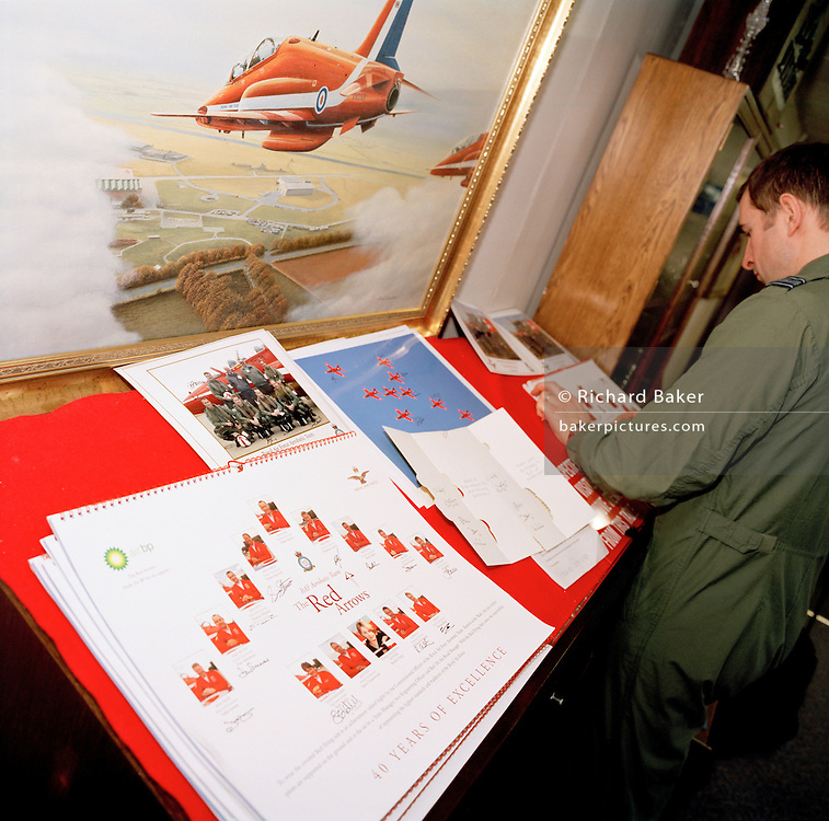 A pilot of the Red Arrows, Britain's RAF aerobatic team signs team publicity posters.