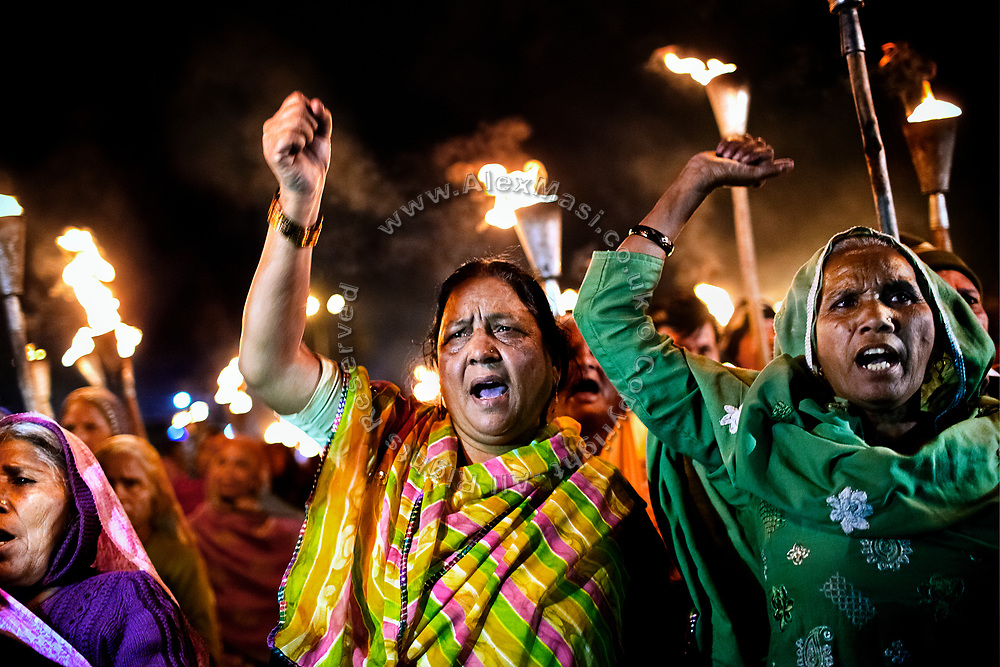 Fist up towards the sky, Rashida Bee, 57, (centre) is demonstrating along other 1984 'survivors' next to the abandoned Union Carbide (now DOW Chemical) industrial complex in Bhopal, central India, on the evening of the 29th anniversary since the infamous 'Gas Disaster', on December 2, 2013. Rashida Bee is the founder of 'Chingari Trust Rehabilitation Centre', one of two vital medical institutions funded by 'The Bhopal Medical Appeal'.