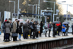 © Licensed to London News Pictures. 04/01/2016<br /> Cold and wet January weather for commuters this morning (04.01.2016)<br /> London commuters standing at Pettswood train station Pettswood,Kent on their first day back to work in 2016.<br /> (Byline:Grant Falvey/LNP)