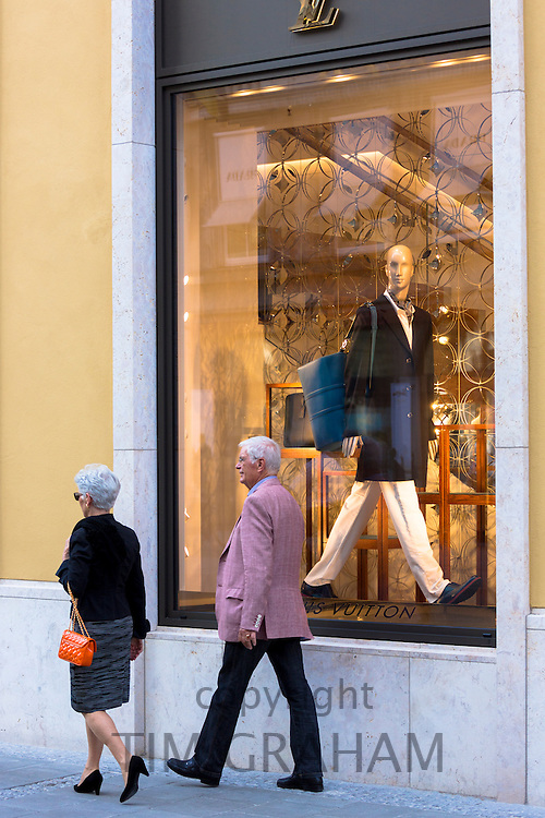 Stylish couple walking past Louis Vuitton shop in Residenzstrasse in Munich, Bavaria, Germany