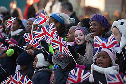 © Licensed to London News Pictures. 07/02/2012. LONDON, UK. School children cheer and wave flags as they wait for the Kings Troop Royal Horse Artillery to parade through Woolwich. Gunners of the Kings Troop, previously based at St John's Wood since 1947, today (07/02/12) today arrived at their new home at Napier Barracks in Woolwich Photo credit: Matt Cetti-Roberts/LNP