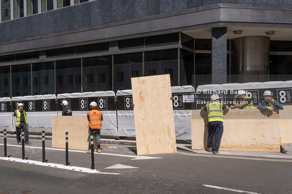 Construction workmen pause before carrying new plyboards into a nearby site on Threadneedle Street in the City of London, the capital's financial district, on 8th June 2021, in London, England.