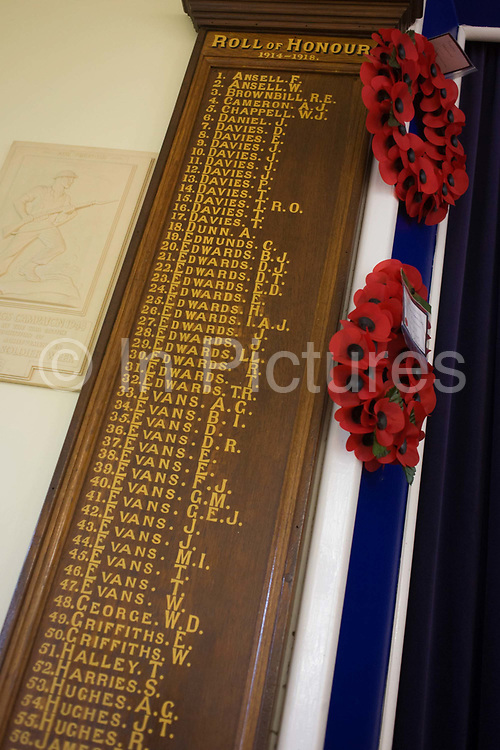 The names of Welshmen who served (but not necessarily killed) in the First World War are listed on a memorial in the village hall of Tregaron, Wales, UK. Typical Welsh names such as Evans and Davies are seen numbered from 1 to 56 and beyond. Their vertical listing remembers the service of the local men (and possibly women) whose youth passed in the years of this worldwide wartime. Two wreaths of poppies are attached to the top in this quiet corner of the village hall in mid-Wales.