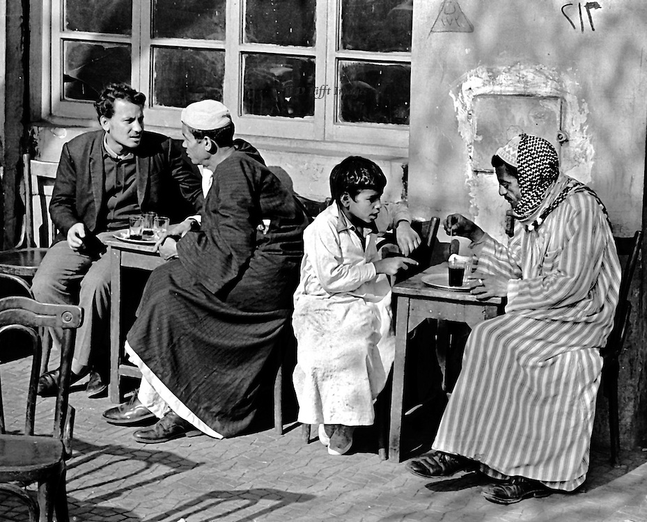 Two pairs, three men and one boy, seated at tiny tea house tables, deep in conversation.  One of the men wears trousers and modern dress, the other two and the boy wear the traditional galabeyya.  All are deep into their talk, intent on their subjects, one obviously speaking and the other listening.