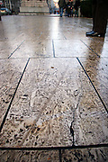 Muddy footprints and bike trails line a patch of marble stones in Rouen, France.