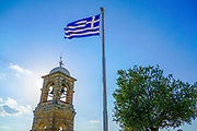 Greek flag and the Belfry of Saint George (Agios Georgios) chapel at the top of the Lycavittos hill in Athens, Greece as seen at sunset