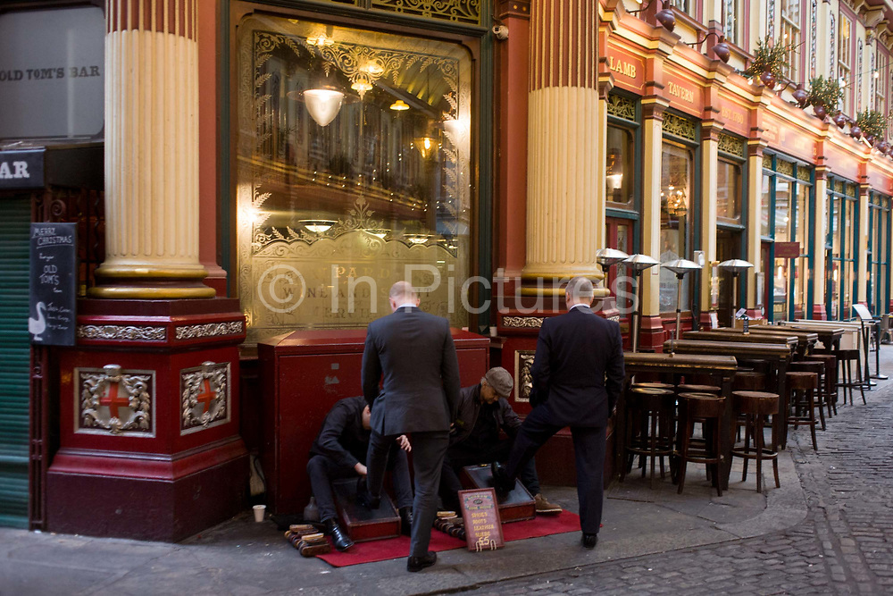 City businessmen have their shoes shined in Leadenhall Market, a few days before Christmas. Standing in matching poses, the men have left feet up on the shoesshiners' polishing equipment in the central part of this Victorian covered marketplace. Shoe-shiners are a traditional location to operate where city gentlemen pass-by on their way to meetings or lunches nearby. Leadenhall Market is one of the oldest markets in London, dating from the 14th century and is in the historic centre of the City of London financial district aka The Square Mile, founded by the Romans in the 1st Century.
