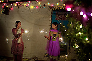Poonam, 12, (right) is celebrating Diwali, the Hindu festival of lights, next to her oldest sister Arti, 18, while in the front yard of their newly built home in Oriya Basti, one of the water-contaminated colonies in Bhopal, central India, near the abandoned Union Carbide (now DOW Chemical) industrial complex, site of the infamous '1984 Gas Disaster'.