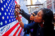 19 SEPTEMBER 2011 - NEW YORK, NY: Women sign an American flag used as a condolences card for firefighters at the firehouse for Battalion 9, Ladder 4, Engine 54 on 8th Ave at 49th Street in Manhattan, Sept. 19, 2001. Fifteen firefighters from the station were killed in the terrorist attack on the World Trade Center Towers that took place on Sept. 11, 2001. More than 2,900 people, including hundreds of New York firefighters were killed when terrorists crashed two airliners into the towers. .PHOTO BY JACK KURTZ