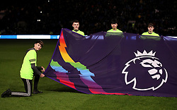 A Premier League flag is held up before the game featuring rainbow colours, supporting the Stonewall campaign