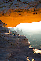 An orange glow illuminates Mesa Arch at sunrise, Canyonlands National Park, Utah