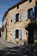 Scene in the medieval village of Lagrasse, Languedoc-Roussillon, France. Lagrasse is known as one of the most beautiful French villages. It lies in the valley of the River Orbieu and is famous for its stone bridge and The Abbey of St. Mary of Lagrasse, Abbaye Sainte-Marie de Lagrasse, a Romanesque Benedictine abbey.
