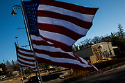 PARADISE, CA - NOVEMBER 08: American flags fly along Skyway Road, in front of still empty lots and a structure affected by fire, during the one year anniversary of the Camp Fire on November 8, 2019 in Paradise, California. It has been one year since the Camp Fire, caused by PG&E transmission lines, tore through the town of Paradise, California, killing 85 people and destroying more than 18,000 homes and businesses, becoming the deadliest and most destructive fire in the history of California. (Photo by Philip Pacheco/Getty Images)