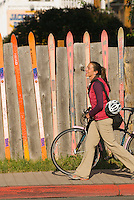 A young woman walks her bike along the sidewalk in Jackson, Wyoming.