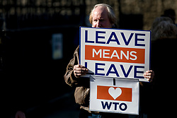 """© Licensed to London News Pictures. 14/02/2019. London, UK. A Brexit supporter holds a """"LEAVE MEANS LEAVE"""" placard outside the Palace of Westminster. MPs continue to debate Brexit in Parliament, and will vote on a series of amendments today. Photo credit: Rob Pinney/LNP"""