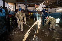 © Licensed to London News Pictures. 29/12/2015. York, UK. Royal Electrical and Mechanical Engineer soldiers help sweep flood damage  from the floor at a mechanics business on Huntington Road in York on December 29, 2015. Further rainfall is expected over coming days as Storm Frank approaches the east coast of the country. Photo credit: Ben Cawthra/LNP