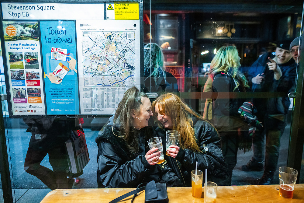 © Licensed to London News Pictures. 12/04/2021. Manchester, UK. People drinking at tables set in bus shelters in Stevenson Square on a night out in Manchester City Centre as government restrictions to control the spread of Coronavirus are eased across the UK. Pubs, restaurants, hairdressers, gyms and non essential retailers are now permitted to serve customers within restrictions. Photo credit: Joel Goodman/LNP