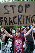 Balcombe, West Sussex. Site of Cuadrilla drilling. Demonstration against fracking 18.08.2013. A young protester holds up a sign saying 'Stop fracking'.
