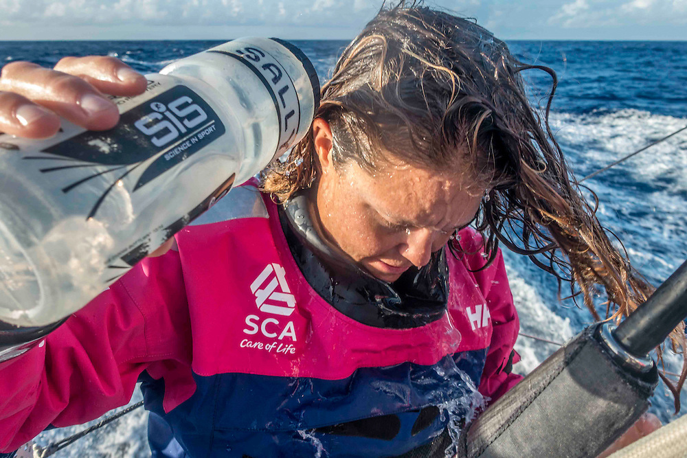 April 27, 2015. Leg 6 to Newport onboard Team SCA. Day 8. Stacey Jackson rinses her hair from the salty water.
