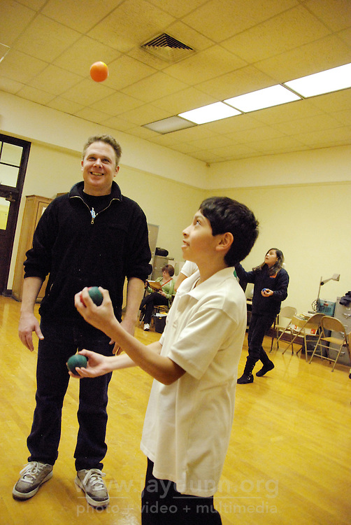 """USA, Chicago, IL, December 12, 2009.  Instructor Douglas Grew checks a student's juggling progress. Students in the """"At-Risk After School Program"""" at Maria Saucedo Scholastic Academy receive training in basic physics principles through an innovative new program called """"Circus Galactica"""" put on by Pros Arts, a non-profit organization founded in 1978 by professional artists dedicated to the Pilsen/Little Village communities. In a residency that directly integrates science and art, veteran circus performers Douglas Grew and Paul Lopez bring the importance of """"balance, focus and presentation"""" into hands-on lessons about gravity, inertia, and the dynamics of objects in motion. Photo for Hoy by Jay Dunn."""
