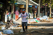 26 DECEMBER 2013 - BANGKOK, THAILAND: An anti-government protestor walks past debris in the street during a lull in rioting against Thai police at the Thai Japan Stadium. Thousands of anti-government protestors flooded into the area around the Thai Japan Stadium to try to prevent the drawing of ballot list numbers by the Election Commission, which determines the order in which candidates appear on the ballot of the Feb. 2 election. They were unable to break into the stadium and ballot list draw went as scheduled. The protestors then started throwing rocks and small explosives at police who responded with tear gas and rubber bullets. At least 20 people were hospitalized in the melee and one policeman was reportedly shot by anti-government protestors.      PHOTO BY JACK KURTZ