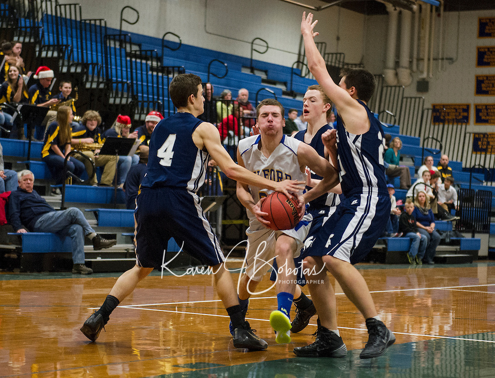 Gilford's Davis Nast muscles through White Mountain's  Timmy Voight and Jacob Wood during Friday night NHIAA Division III Basketball.  (Karen Bobotas/for the Laconia Daily Sun)