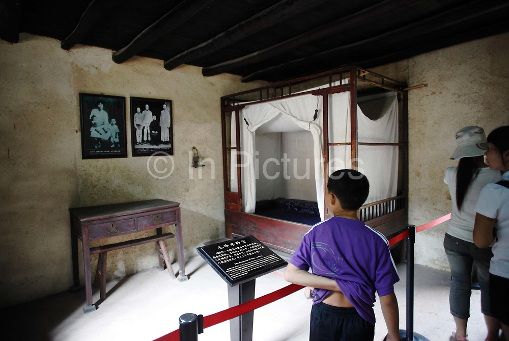 Visitors walk through Mao Zedong's bedroom at his former home and birthplace in Shaoshan, Hunan Province, China on 12 August 2009.  The village of Shaoshan, in rural Hunan Province, is tiny in size but big in name. It was the childhood home for Mao Zedong, the controversial revolutionary who came from obscurity but eventually defied all odds conquered China in the name of communism. Now his home, a sacred place among China's official propaganda, is in reality a microcosm of the country itself: part commercialism, part superstition, with a dash of communist ideological flavor.