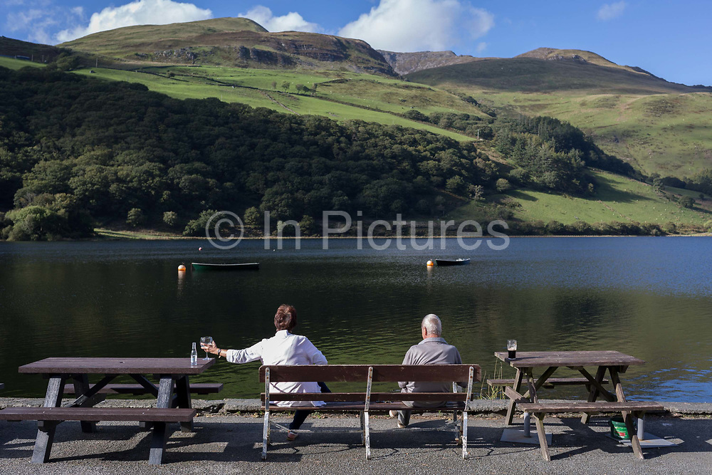 Visitors sit overlooking Lake Tal-Y-Llin and in the distance, the 2,928ft mountain Cader Idris, on 12th September 2018, near Dolgellau, Gwynedd, Wales.