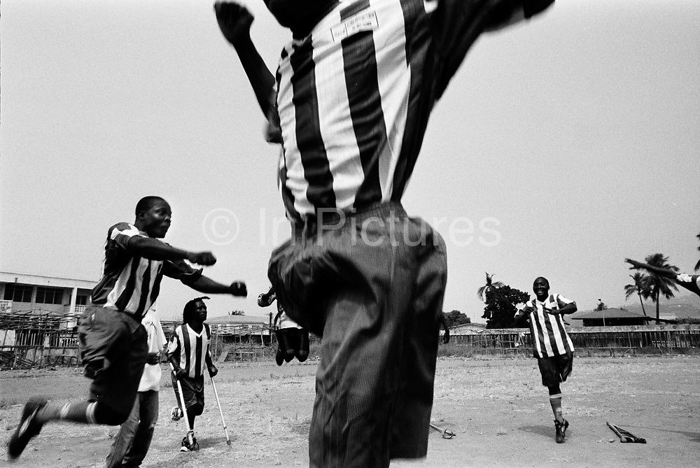 Members of the Amputee Football Team practice heading the ball before an exhibition match to mark the opening of the Special Court in Sierra Leone. At the last minute they were told that they?Äôd have to play their match on the practice ground of the National Sadium instead of the main pitch. The anticipated crowd never came. Freetown, Sierra Leone 2004..Rebel forces, the Revolutionary United Front in Sierra Leone, systematically murdered, mutilated, and raped civilians during the country's civil war as a policy of terror