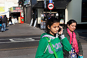 Young girl on her mobile phone in Southall in West London, also known as 'Little India' by some, is an area almost completely populated by people from South Asia. Figures show that the area is approximately 50 percent Indian in origin although walking the streets it would appear far higher as the local people go about their shopping in the many shops specialising in goods specific to this culture. The mix of religions is mainly Sikh, Hindu and Muslim.<br /> <br /> Southall is primarily a South Asian residential district. 1950 was when the first group of South Asians arrived in Southall, reputedly recruited to work in a local factory owned by a former British Indian Army officer. This South Asian population grew due to the closeness of expanding employment opportunities. The most significant cultural group to settle in Southall are Indian Punjabis.