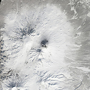 """Five Volcanoes Erupting at Once<br /> <br /> Remote. Cold. Rugged. Those three adjectives capture the essence of Russia's Kamchatka Peninsula. Another word—perhaps more applicable than anywhere else on Earth—is """"fiery.""""<br /> Of the roughly 1,550 volcanoes that have erupted in the recent geologic past, 113 are found on Kamchatka. Forty Kamchatkan volcanoes are """"active,"""" either erupting now or capable of erupting on short notice. The Operational Land Imager (OLI) on Landsat 8 captured activity at five of them during a single satellite pass on April 14, 2014.<br /> From geographic north to south (and top to bottom on this page), the volcanoes are Shiveluch, Klyuchevskaya, Bezymianny, Kizimen, and Karymsky. The tallest of the group is Klyuchevskaya, a stratovolcano with a steep, symmetrical cone that reaches 4,750 meters (15,580 feet) above sea level. The most active is Karymsky, a 1,536-meter (5,039-foot) peak that has erupted regularly since 1996.<br /> Plate tectonics is responsible for the many volcanoes on Kamchatka Peninsula. The Pacific Plate is slowly colliding with and sliding beneath the Okhotsk Plate. As rock from the Pacific Plate descends and encounters higher pressures and temperatures, it melts into magma. Over time, magma accumulates and migrates up toward the surface, causing volcanic eruptions.<br /> Long before the discovery of plate tectonics, Kamchatka's many volcanoes and eruptions were woven into a rich tapestry of myths and creation stories. According to Koryak folklore, the raven-like deity Kutkh created Kamchatka by dropping a giant feather on the Pacific Ocean. Each of the first generation of men became one of Kamchatka's mountains at death; many of these mountains became volcanic because the men's hearts burned so passionately for a beautiful woman that Kutkh had also created near the beginning of time.<br /> Photo Shows klyuchevskaya<br /> ©Earth Observatory/Exclusivepix"""