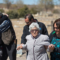 Martha Muñoz and Jessie Muñoz help lead their mother Ramona Muñoz back to her seat at the burial plot for their grandparents at Hillcrest Cemetery in Gallup Saturday. Members of the Muñoz family, who live in Los Angeles, have been researching their family history and discovered the unmarked grave site of Dolores and Fernando Muñoz.