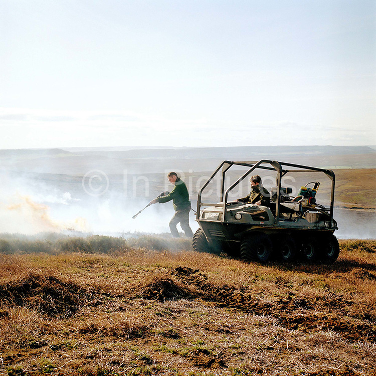 Gamekeeper, Charlie Woof, puts out the fire with water after heather burning, Bransdale shooting estate, North York Moors, North Yorkshire, UK.  Heather is burnt to regenerate it, the more patches there are on the moor the better it is, producing more habitat for the grouse, and that has a knock on effect for the wader population as well.