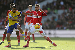 Leeds United's Kemar Roofe (left) and Middlesbrough's Lewis Wing during the Sky Bet Championship match at The Riverside Stadium, Middlesbrough.
