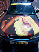 A bizzarely customized car has a photograph of a woman lying across the bonnet. London